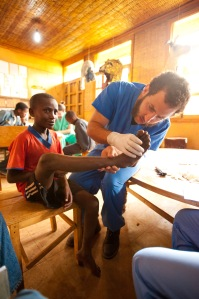Medical Volunteer at Common River, Aleta Wondo, Ethiopia looking at a childs hurt foot