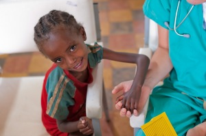 malourished girl in Ethiopia getting help from a medical volunteer