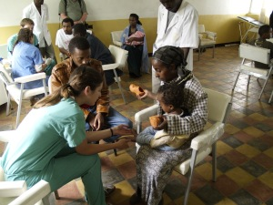 Medical Volunteer in Ethiopia helping a woman anc child